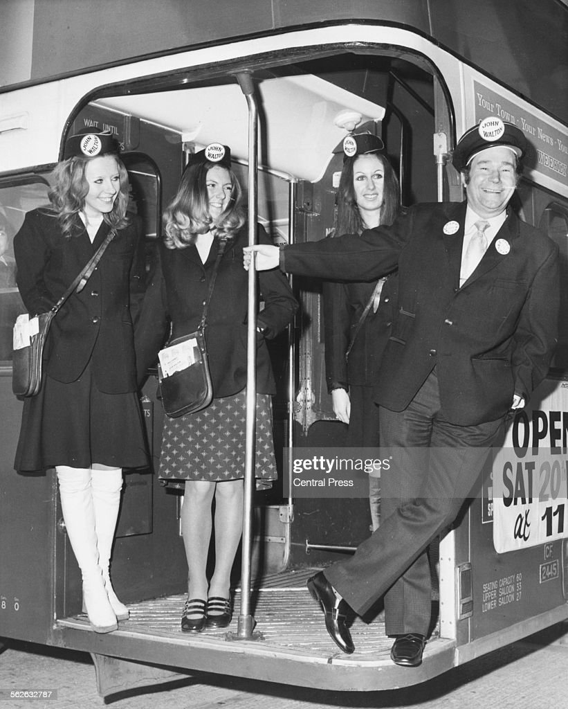 Portrait of actor Reg Varney, star of television show 'On the Buses', posing with three women 'clippies' on the deck of a bus in Chelmsford, Essex, November 20th 1971.