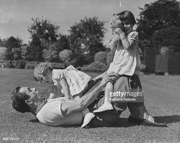 Portrait of actor Tyrone Power playing on the grass with his young daughters Romina and Taryn circa 1955