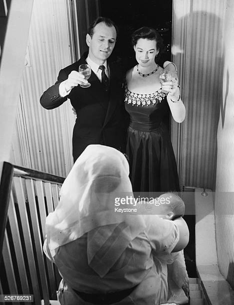 Portrait of actors and spouses Nigel Patrick and Beatrice Campbell toasting their baby son Simon held by a nurse following his christening at their...