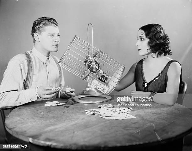 Portrait of actors Dolores del Rio and Ralph Forbes playing a card game as they appear in the film 'The Trail of 98' for MGM Studios June 6th 1927