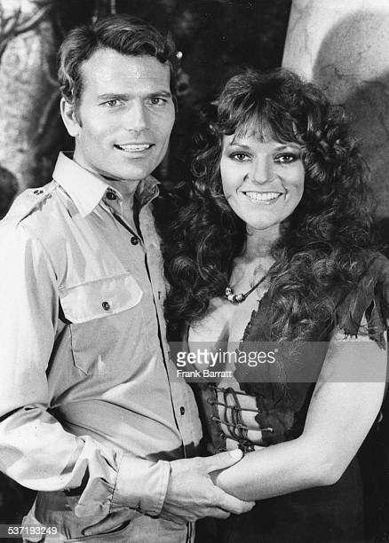 Portrait of actors Pat Wayne and Dana Gillespie on the set of the movie 'The People That Time Forgot' at Pinewood Studios London March 1st 1977