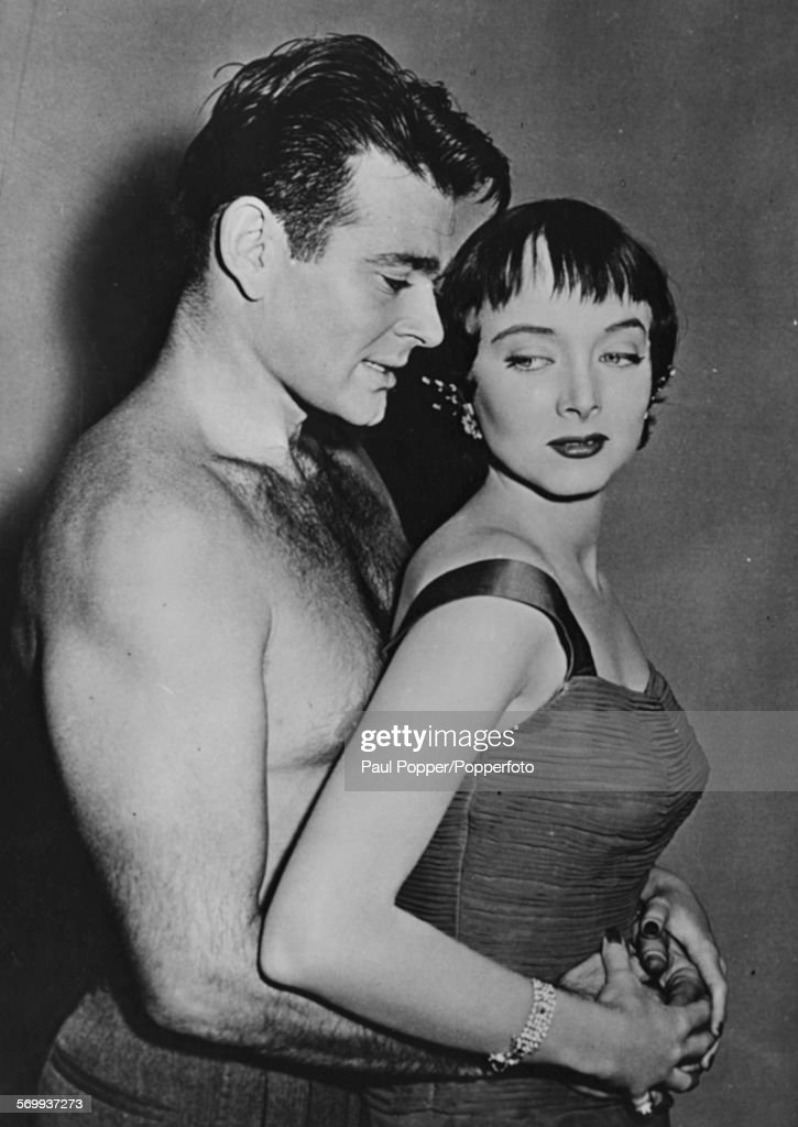 Portrait of actors Stuart Whitman and Carolyn Jones (1930-1983) in a romantic embrace, as they appear in the movie 'Johnny Trouble', September 30th 1957.