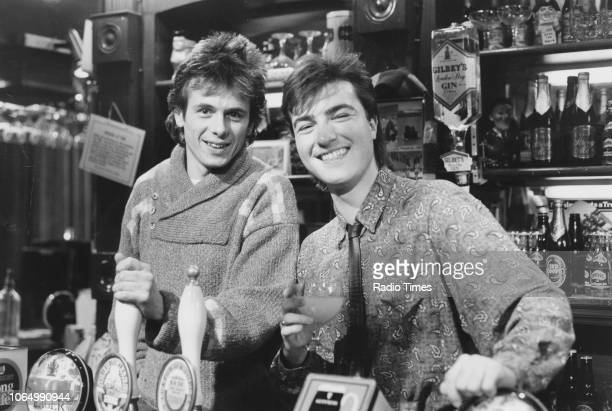 Portrait of actors Tom Watt and Nick Berry behind the bar of 'The Queen Victoria' pub on the set of the television soap opera 'EastEnders' January...