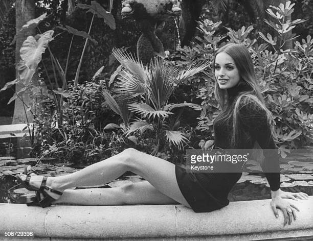 Portrait of actress Adrienne La Russa star of the film 'Salvare la faccia' wearing a mini skirt and sitting on the edge of a pond Rome September 1969