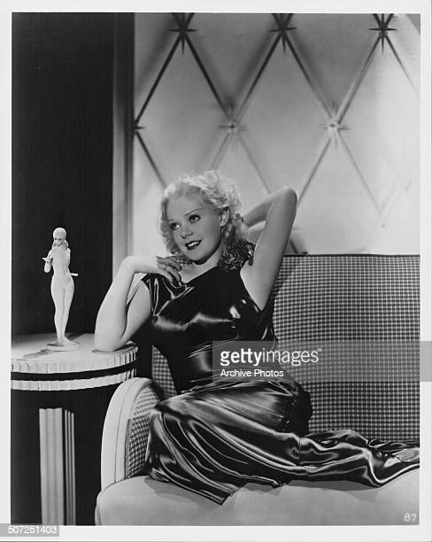 Portrait of actress Alice Faye wearing an evening dress with her legs up an a couch circa 1935