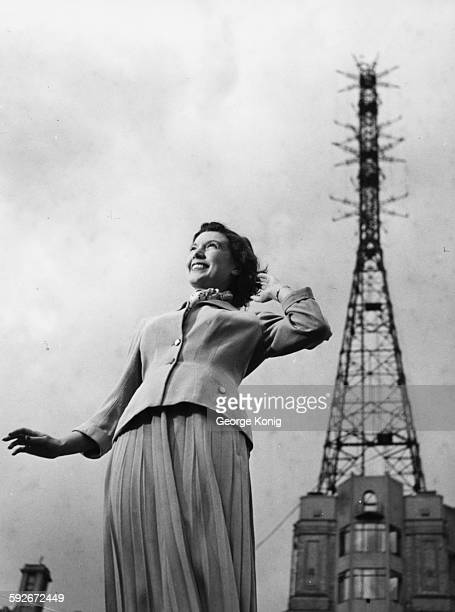 Portrait of actress and BBC television announcer Sylvia Peters standing in front of Alexander Palace London circa 1950