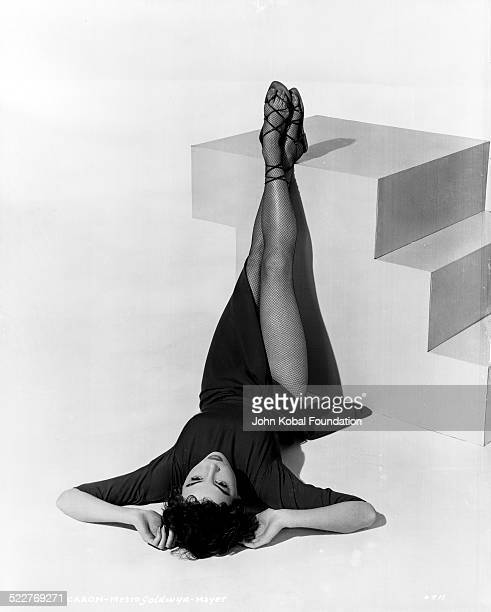 Portrait of actress and dancer Leslie Caron lying down with her legs propped up as she appears in the movie 'An American in Paris' with MGM Studios...