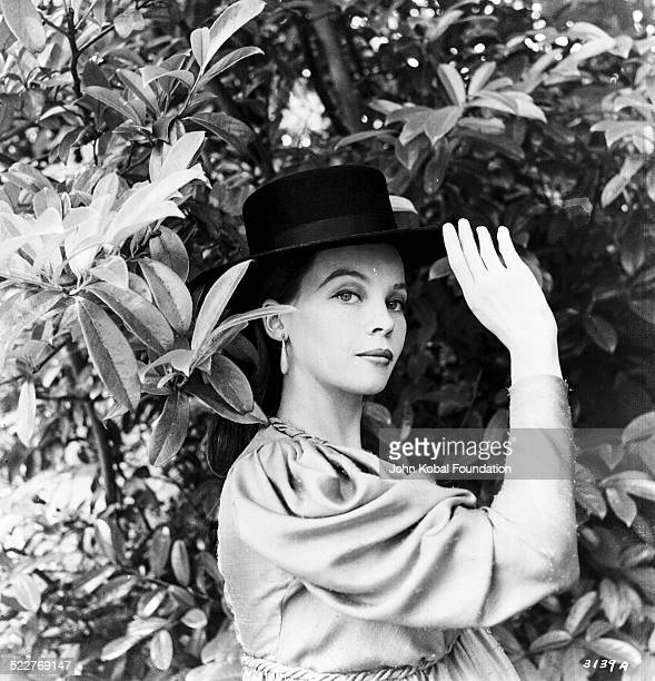 Portrait of actress and dancer Leslie Caron standing in a garden wearing a hat with MGM Studios October 6th 1958
