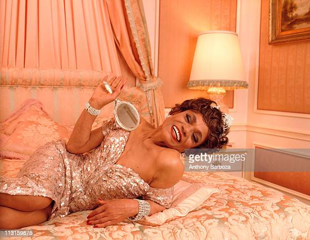 Portrait of actress and singer Eartha Kitt smiling and holding a mirror while reclining on a bed New York 1992
