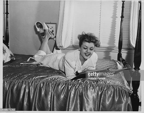 Portrait of actress Angela Lansbury lying on a hotel bed wearing a bathrobe circa 19551965
