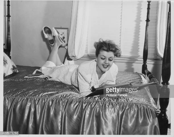 Portrait of actress Angela Lansbury lying on a hotel bed wearing a bathrobe circa 19551965