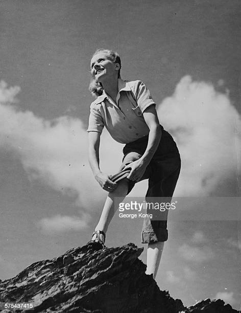 Portrait of actress Ann Todd rolling up her trousers as she walks along a rock outcrop during a holiday in Cornwall England circa 1949
