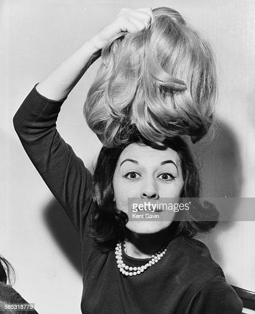 Portrait of actress Anne Rogers holding a blonde wig over her brunette hair which she will be wearing for her role in the musical 'She Loves Me' at...