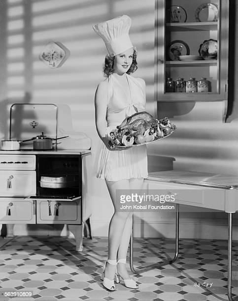 Portrait of actress Arlene Dahl holding a roast chicken and wearing a chef hat for Warner Bros Studios 1946