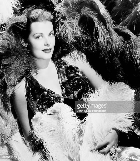 Portrait of actress Arlene Dahl lying amongst a sea of feathers for Warner Bros Studios 1946