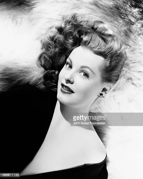 Portrait of actress Arlene Dahl reclining back on a fur rug, for Warner Bros Studios, 1946.