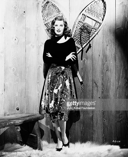 Portrait of actress Arlene Dahl standing on a fur rug in a log cabin for Warner Bros Studios 1946
