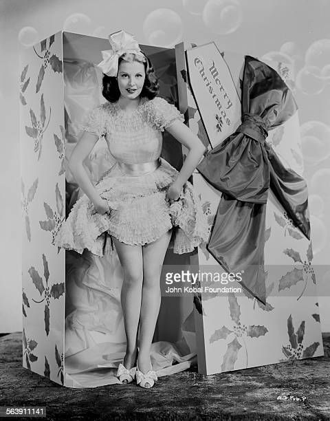 Portrait of actress Arlene Dahl wearing a bow in her hair as she steps out of a huge Christmas present box for Warner Bros Studios 1946