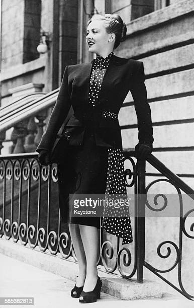 Portrait of actress Audrey Totter modeling an Irene designed skirt suit of sold navy blue wool with a white polka dot gilet standing on a street in...