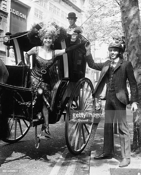 Portrait of actress Barbara Windsor being helped down from a hansom cab by musician Maurice Gibb, at a photocall for the musical 'Sing a Rude Song'...