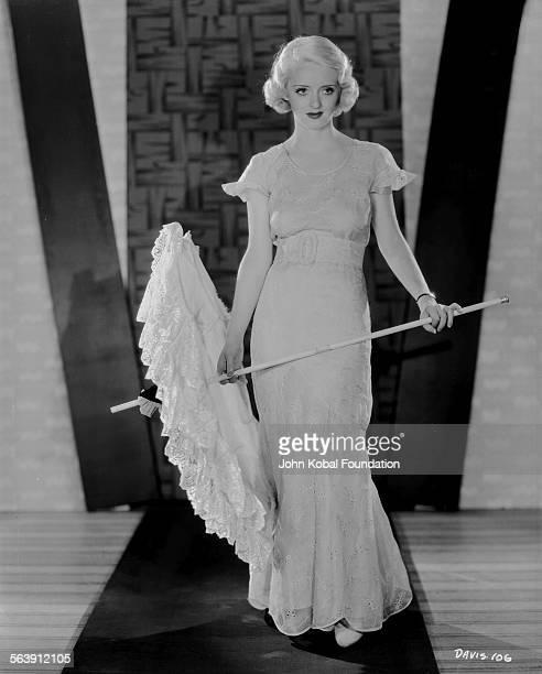 Portrait of actress Bette Davis holding an opened umbrella for Warner Bros Studios 1930