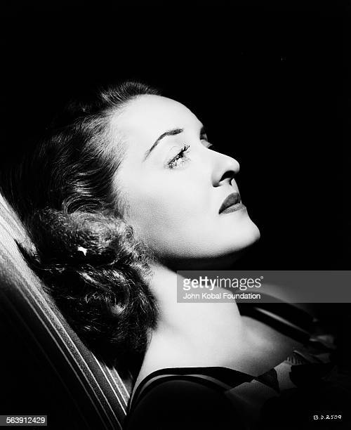 Portrait of actress Bette Davis leaning back with her face bathed in light, for Warner Bros Studios, 1940.
