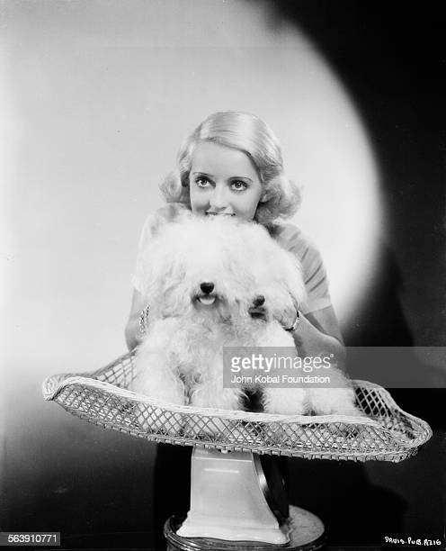 Portrait of actress Bette Davis posing with a dog sitting on a set of scales for Warner Bros Studios 1933