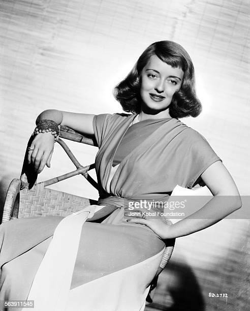 Portrait of actress Bette Davis sitting in a wicker chair for Warner Bros Studios 1942