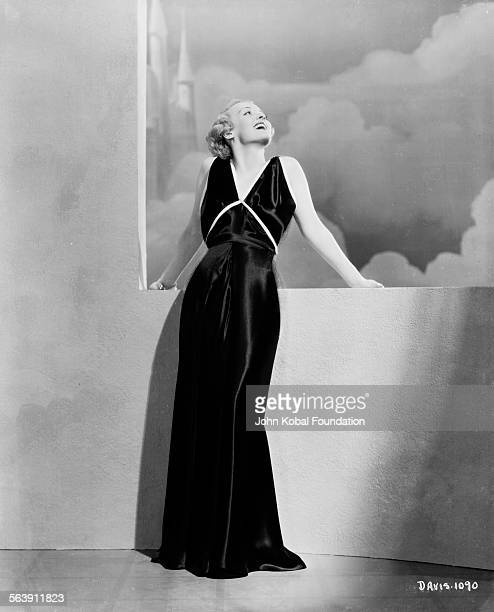 Portrait of actress Bette Davis standing in front of a cloud painted backdrop for Warner Bros Studios 1930