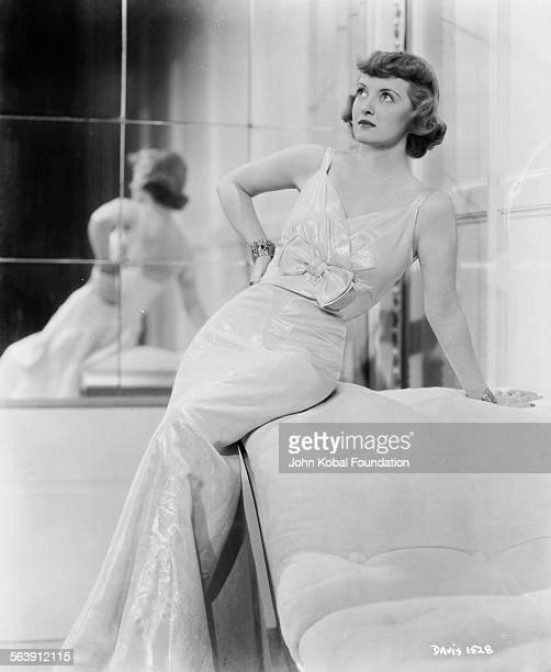 Portrait of actress Bette Davis wearing a ballgown in front of a mirrored wall for Warner Bros Studios 1931