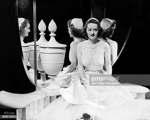Portrait of actress Bette Davis wearing a circle cap and leaning with her back to a mirror for Warner Bros Studios 1939