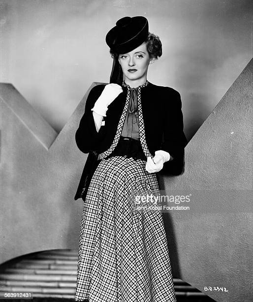Portrait of actress Bette Davis wearing a circular hat and white gloves for Warner Bros Studios 1939