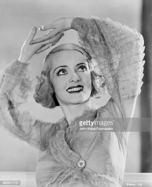 Portrait of actress Bette Davis wearing a dress with ruffled sleeves for Warner Bros Studios 1930