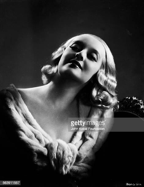 Portrait of actress Bette Davis wearing a fur shawl for Warner Bros Studios 1932