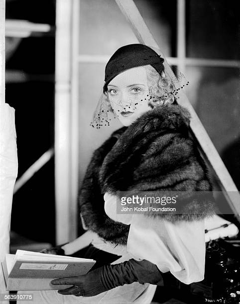 Portrait of actress Bette Davis wearing a fur stole and veiled hat for Warner Bros Studios 1933