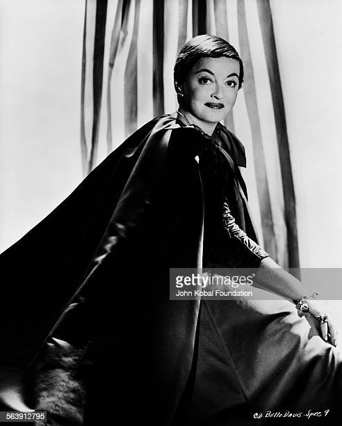 Portrait of actress Bette Davis wearing a long cape for Columbia Pictures 1956