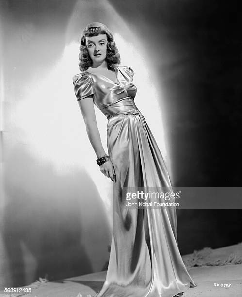 Portrait of actress Bette Davis wearing a long silk dress for Warner Bros Studios 1940