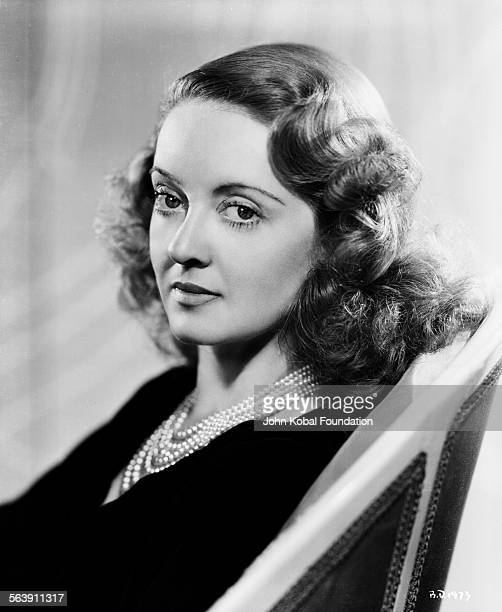 Portrait of actress Bette Davis wearing a pearl necklace for Warner Bros Studios 1937