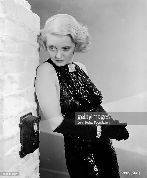 Portrait of actress Bette Davis wearing a sequin gown and long gloves for Warner Bros Studios 1934