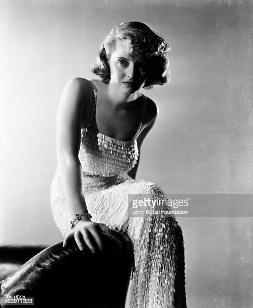 Portrait of actress Bette Davis wearing a tassel sequin dress as she appears in the film 'Marked Woman' for Warner Bros Studios 1937