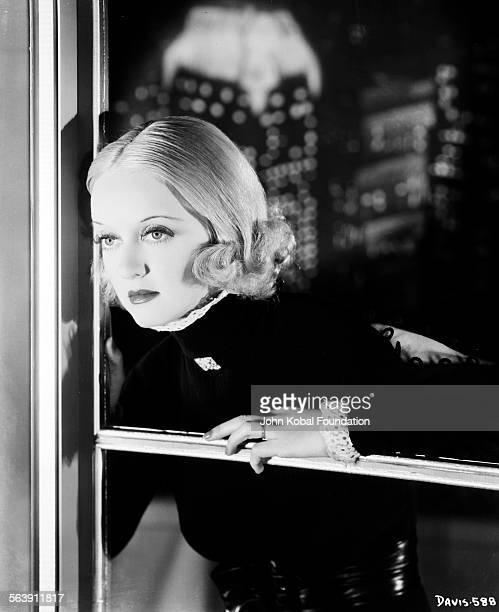 Portrait of actress Bette Davis wearing a turtle neck sweater and leaning out of a window for Warner Bros Studios 1933