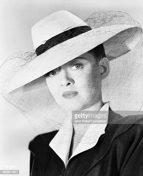 Portrait of actress Bette Davis wearing a veiled hat, as she appears in the film 'Now Voyager', for Warner Bros Studios, 1942.