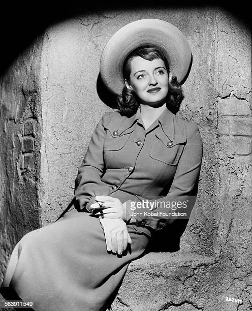 Portrait of actress Bette Davis wearing a wide brimmed hat and smoking a cigarette for Warner Bros Studios 1940