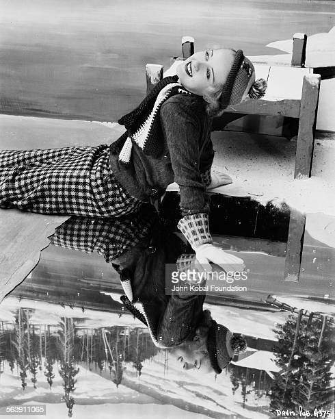 Portrait of actress Bette Davis wearing winter clothes and sitting on a mirror which is acting as a frozen lake for Warner Bros Studios 1934
