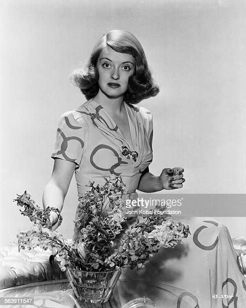 Portrait of actress Bette Davis with a flower arrangement for Warner Bros Studios 1940