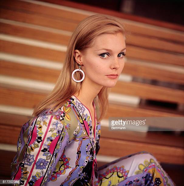 Portrait of actress Carol Lynley wearing a brightly patterned outfit and hoop earings