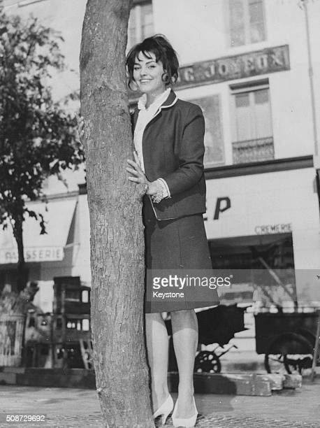 Portrait of actress Catherine Rouvel star of the new film 'Le Coq du Village' standing next to a tree wearing a skirt suit September 26th 1962
