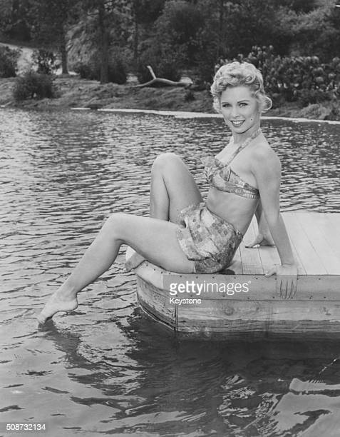 Portrait of actress Cindy Robbins wearing a two piece bathing suit sitting on a jetty with her feet in the water in the Napa Valley California May...