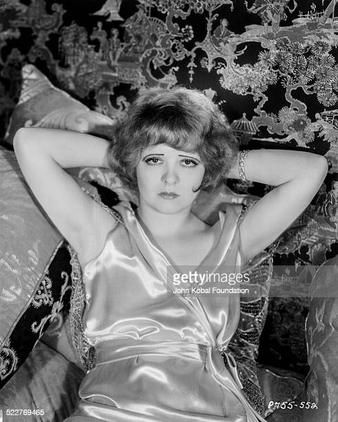 Portrait of actress Clara Bow reclining on a pile of pillows for Paramount Pictures 1929