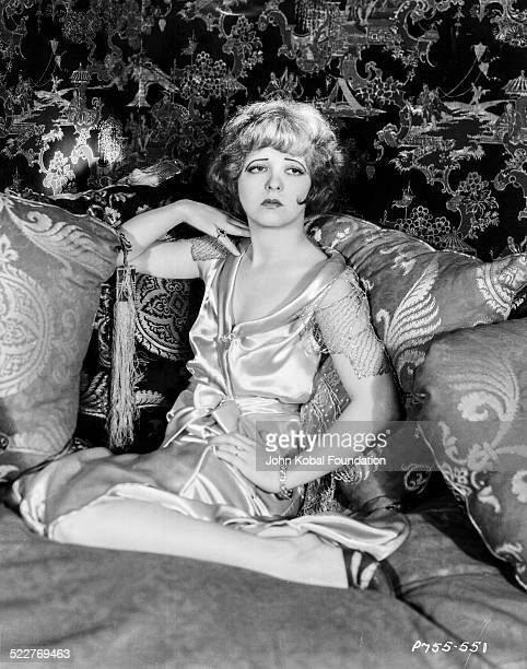 Portrait of actress Clara Bow sitting on a pile of pillows for Paramount Pictures 1926